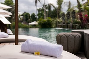 Close up of towel with plumeria frangipani on deck chair at resort pool. Bali island, Indonesia.