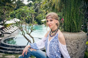 Attractive young woman in ethnic style look posing near the swimming pool, portrait. Tropical island Bali, luxury resort villa, Indonesia.