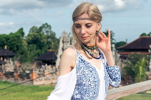 Attractive young woman in ethnic style look posing near the balinese temple, portrait. Tropical island Bali, luxury resort villa, Indonesia.