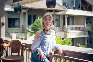Attractive young woman in ethnic style look posing in tropical restaurant, portrait. Tropical island Bali, luxury resort villa, Indonesia.