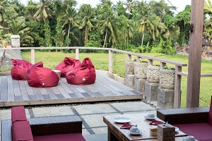 Red pillow soft chairs at a tropical balinese cafe, outside. Bali island, Indonesia.