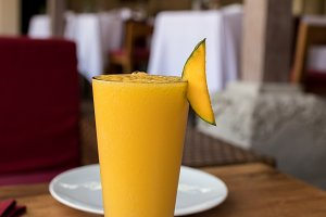 Refreshing glass of tropical mango juice on a wooden table. Bali island, Indonesia.