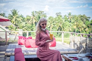 Woman with tropical mango juice outdoors, cafe. Bali island.