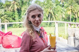 Woman with tropical mango juice outdoors, cafe. Bali island.