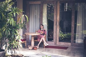 Young sexy woman siiting on chair on her luxury villa. Bali island.