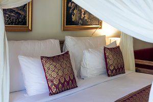 Bed maid up with clean white pillows and bed sheets in beauty room. Close-up. Tropical villa on Bali island, Indonesia.