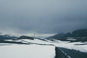 Dark Road through Winter Landscape
