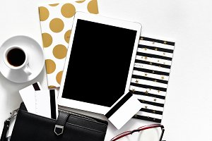 Women's office desk on white background touch pad tablet with gold stylish books black wallet credit cards, top view
