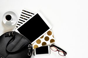 Women's office desk on white background touch pad tablet gadget cellphone with gold stylish books black handbag, top view
