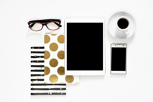 Office desk on white background touch pad tablet gadget cellphone with gold stylish books, top view