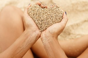 Hands hold sand in shape of heart.