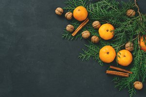 Toned image rustic eco christmas composition tangerines, nuts, cinnamon sticks and natural cypress branches on bark background