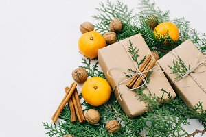 Toned instagram image wrapping rustic eco Christmas gifts with craft paper, string, tangerines and natural cypress branches on white background