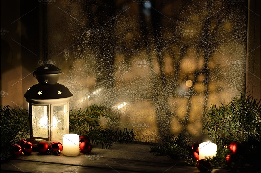 Christmas lantern with snowfall, candles, view from the window on ...