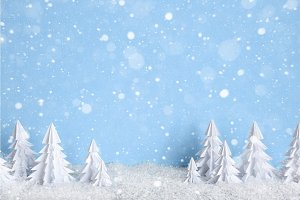Winter Christmas minimalist background with white paper trees on blue  drawing snowflakes