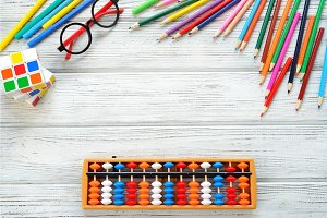 Colorful back to school supplies double border over white table. Mental arithmetic. Space for text.