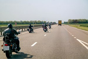 A group of bikers are driving along the highway