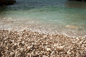 Clear water on pebble beach