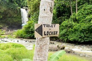 Waterfall deep in the tropical rain forest of Ubud, tropical Bali island, Indonesia. Exotic scene of tropics. Text toilet and locker.