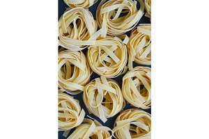 Top view on uncooked nests of tagliatelle pasta