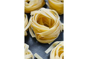 Close-up of uncooked nests of tagliatelle pasta