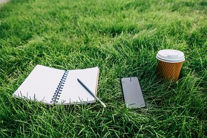 notebook andsmartphone on green lawn