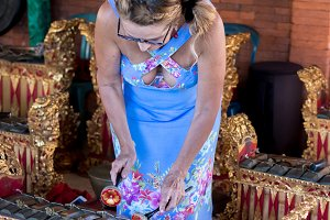 Woman playing on Traditional Balinese music instrument gamelan. Bali island, Indonesia.