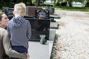Mother and son visiting graveyard