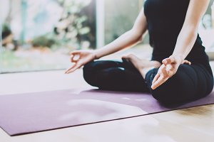 Close up of young woman practicing yoga in a training hall. Freedom concept. Calmness and relax, female happiness.Horizontal, blurred garden on the background.