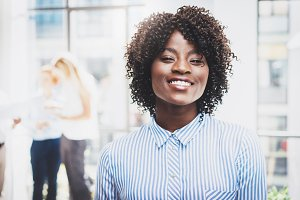 Portrait of young happy black female office worker in modern coworking studio with business team on the background. Horizontal,blurred.