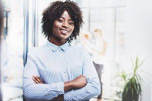 Portrait of happy beautiful african woman standing with arms folded and colleagues on background in modern loft.Businesswoman looking at the camera. Horizontal,blurred.