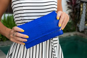 Luxury fashion snakeskin python wallet in woman hands outdoors, shoot near the swimming pool, Bali.