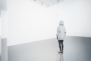 Young woman in modern gallery looking at the blank canvas.