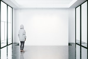 Young woman in empty modern gallery looking at the blank canvas.