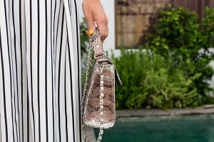 Fashionable woman holding luxury snakeskin python bag. Elegant outfit. Close up of purse in hands of stylish lady. Model posing near the swimming pool. Bali island.