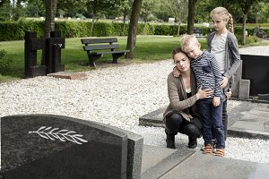 Young family at graveyard mourning