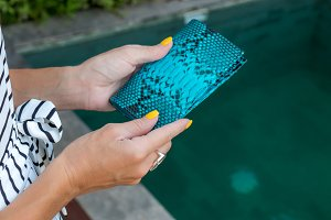Luxury snakeskin python blank passport cover in woman hands. Bali, swimming pool.