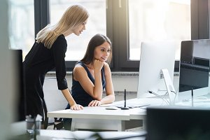 Beautiful women working together in the office on a computer