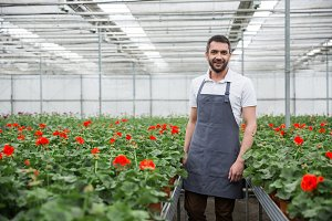 Cheerful young man standing in greenhouse near plants