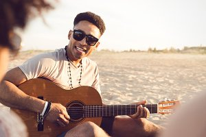 Young afro american man playing guitar for friends