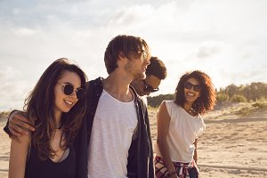 Group of friends walking together on the beach
