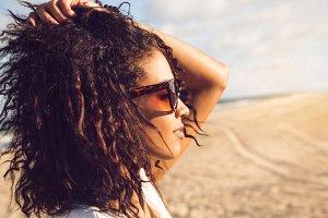 Young afro american woman in sunglasses enjoying sun