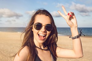 Happy young girl in sunglasses showing peace gesture