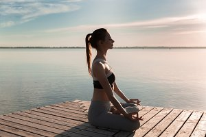 Young sports lady at the beach make meditation exercises.
