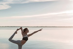 Sports lady standing at the beach make yoga exercises.