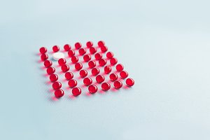 One white round tablet in a grid of red capsules