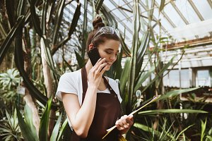 Happy young woman standing in greenhouse talking by phone