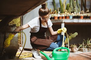 Concentrated young lady in glasses sitting in greenhouse