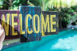 Wooden board with text welcome in man hand. Bali island. Welcome sign.