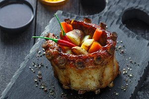 Crown roast of pork ribs with potato and roots, dark photo